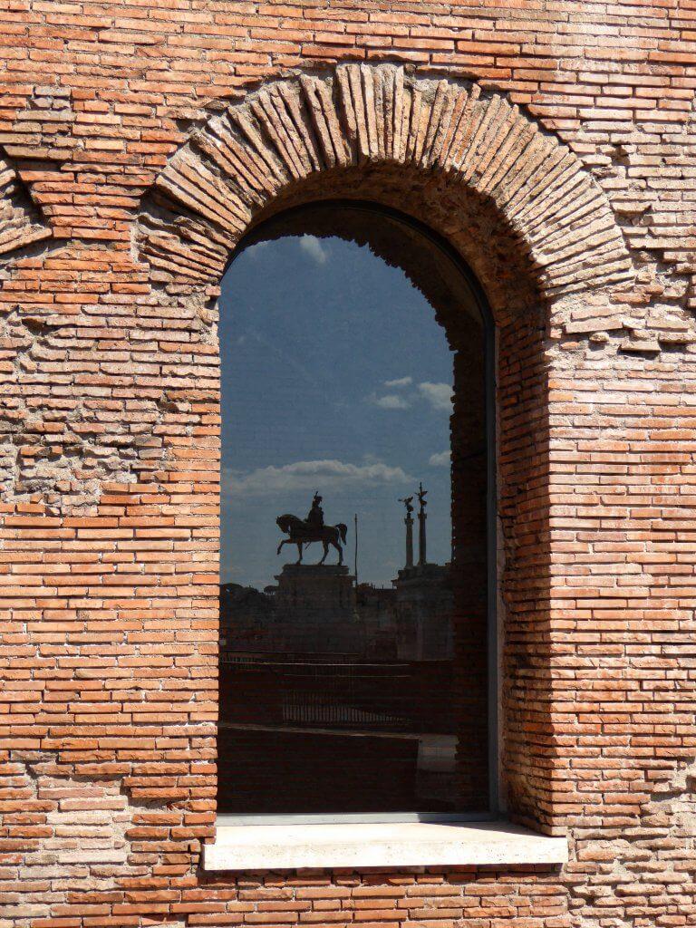 Das Reiterstandbild König Viktor Emanuels II spiegelt sich in einem Fenster der Trajansmärkte